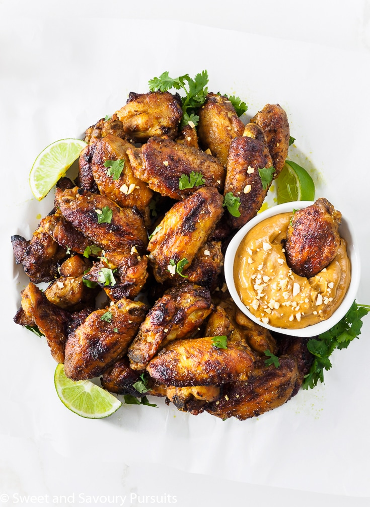 Platter of Thai Baked Chicken Wings with a chicken wing dipped in a bowl of peanut sauce.