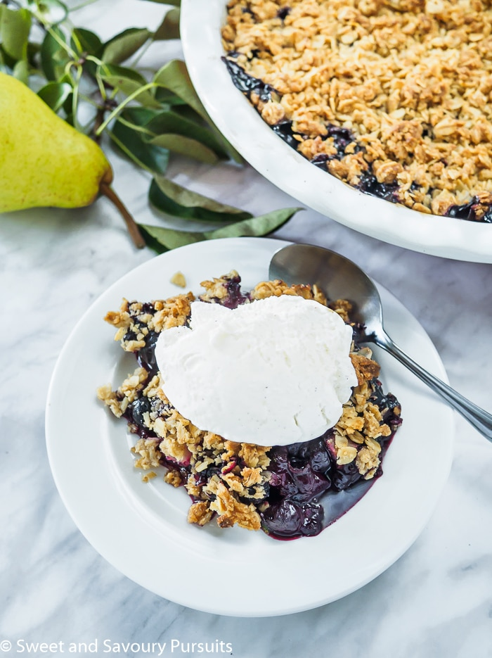 Pear and Blueberry Crumble served with vanilla ice cream.