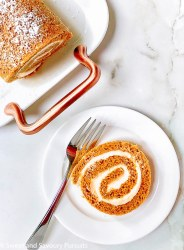A slice of a rolled pumkin cake stuffed with a maple cream cheese swirl.