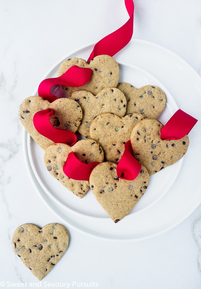Healthier heart-shaped sugar cookies strung on red ribbon.