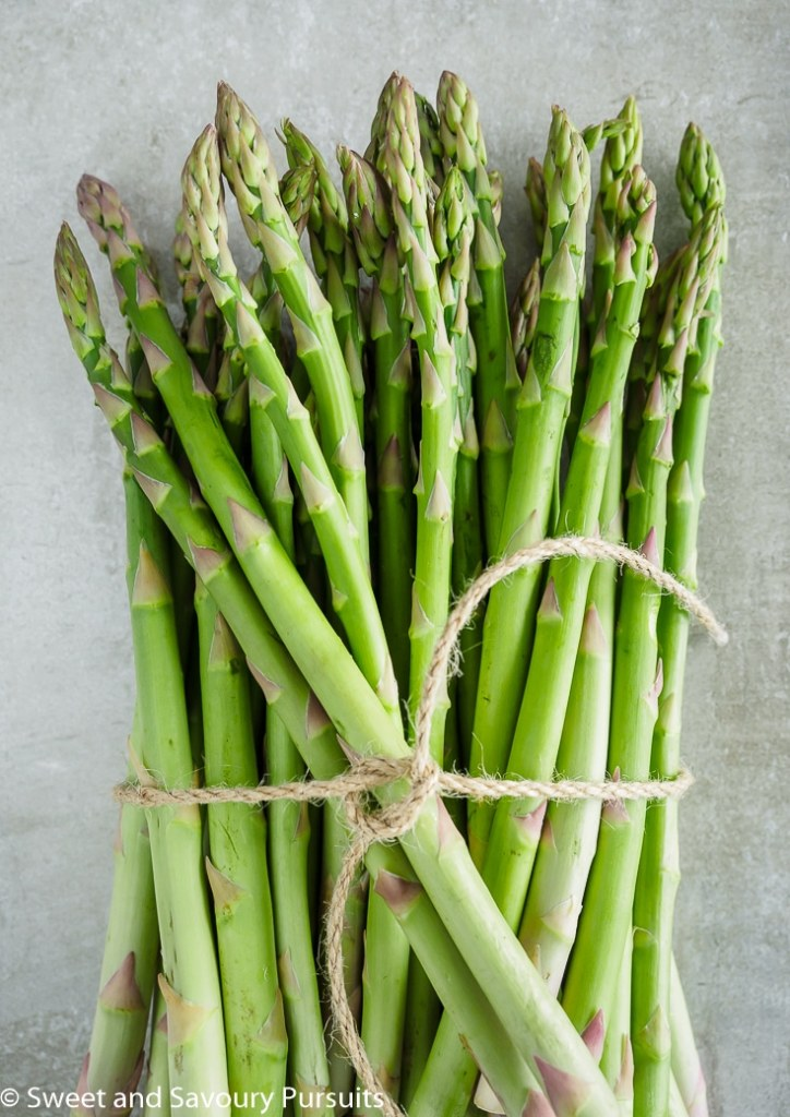 A bunch of fresh asparagus tied with kitchen twine.