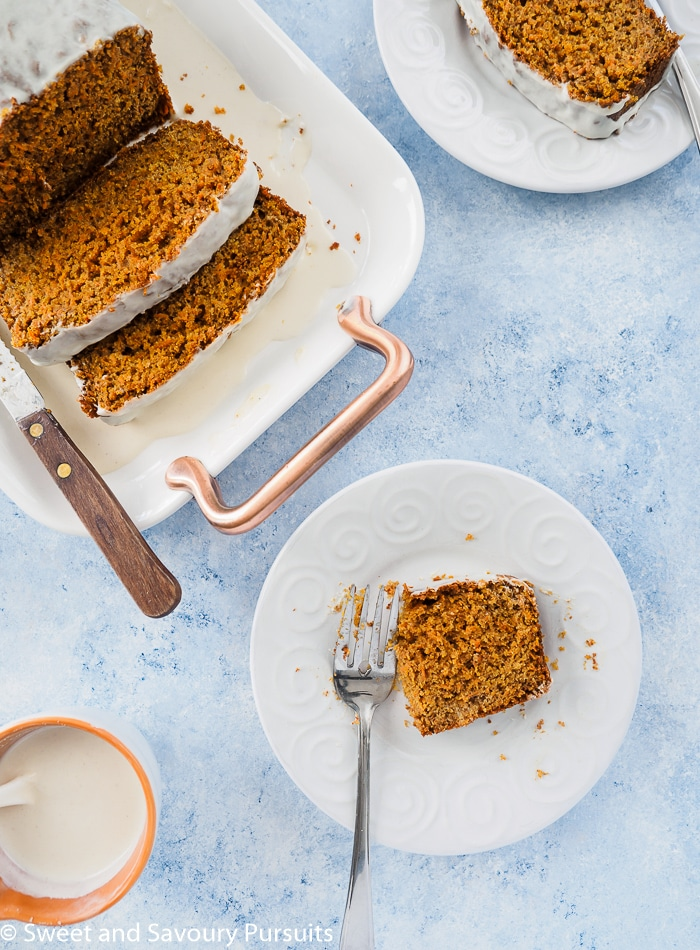 Top view of a partially eaten slice of a Healthy Carrot Bread served with extra icing on the side.