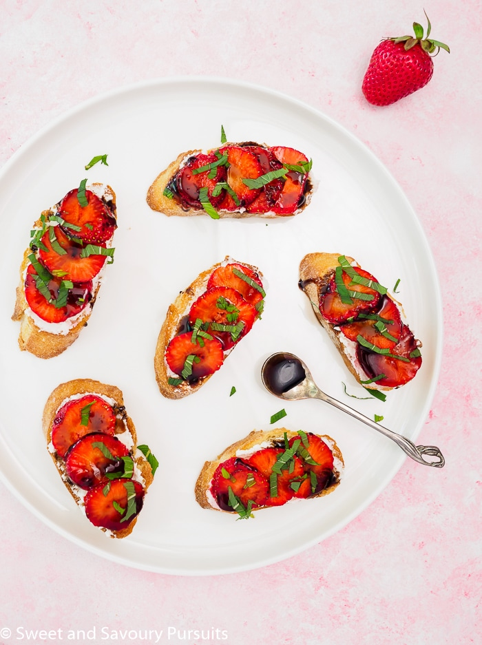 Strawberry Goat Cheese Crostini drizzled with a balsamic reduction on a plate.