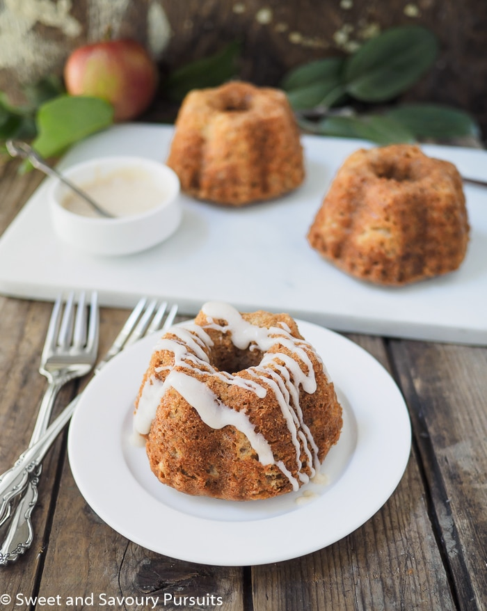 Three Mini Apple Spice Bundt Cakes with drizzle on one cake.
