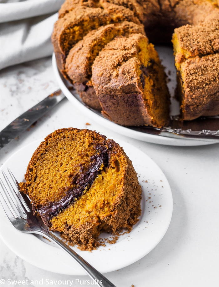 A Pumpkin Chocolate Swirl Bundt Cake on a white dish with the remainder of the cake in the background.