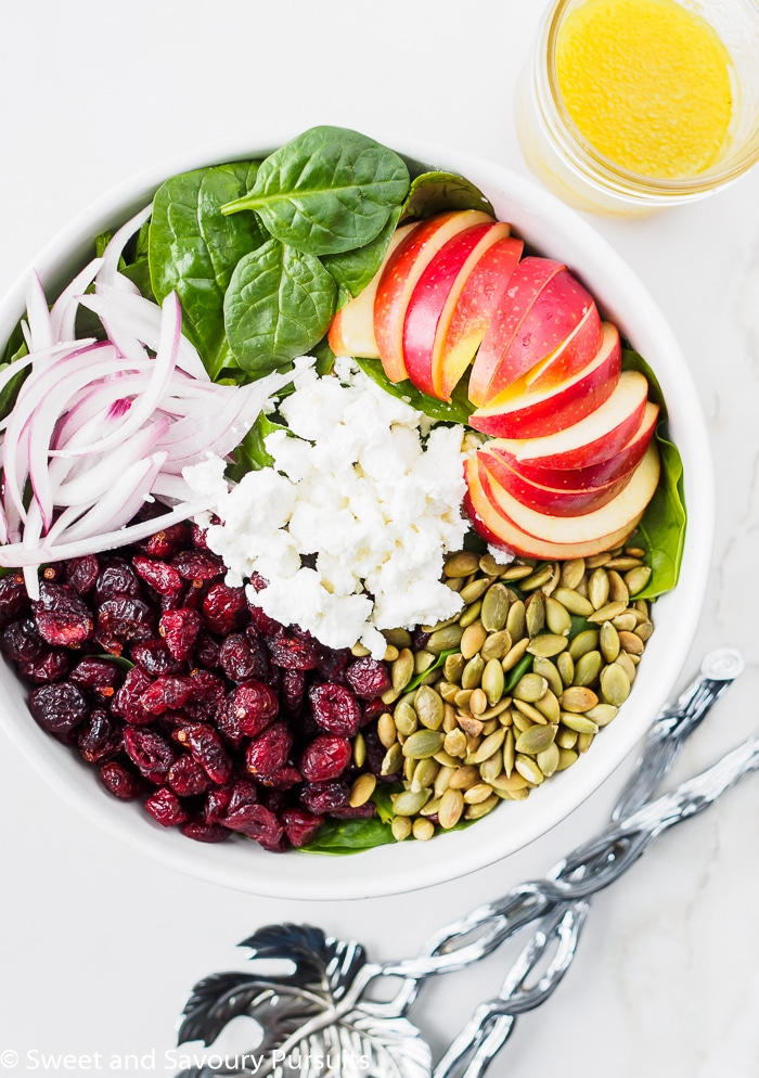Large Bowl of Spinach Salad topped with apples, cranberries, pumpkin seeds and goat cheese.