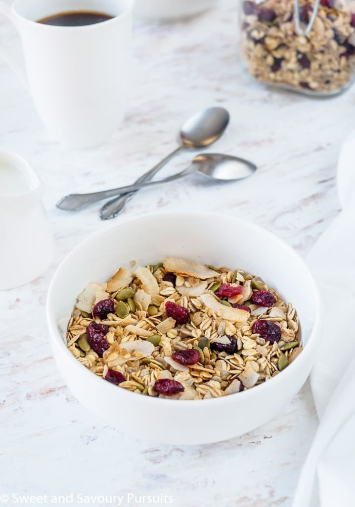 Bowl of homemade muesli made with oats, coconut flakes, pumpkin seeds, sunflower seeds and dried cranberries.