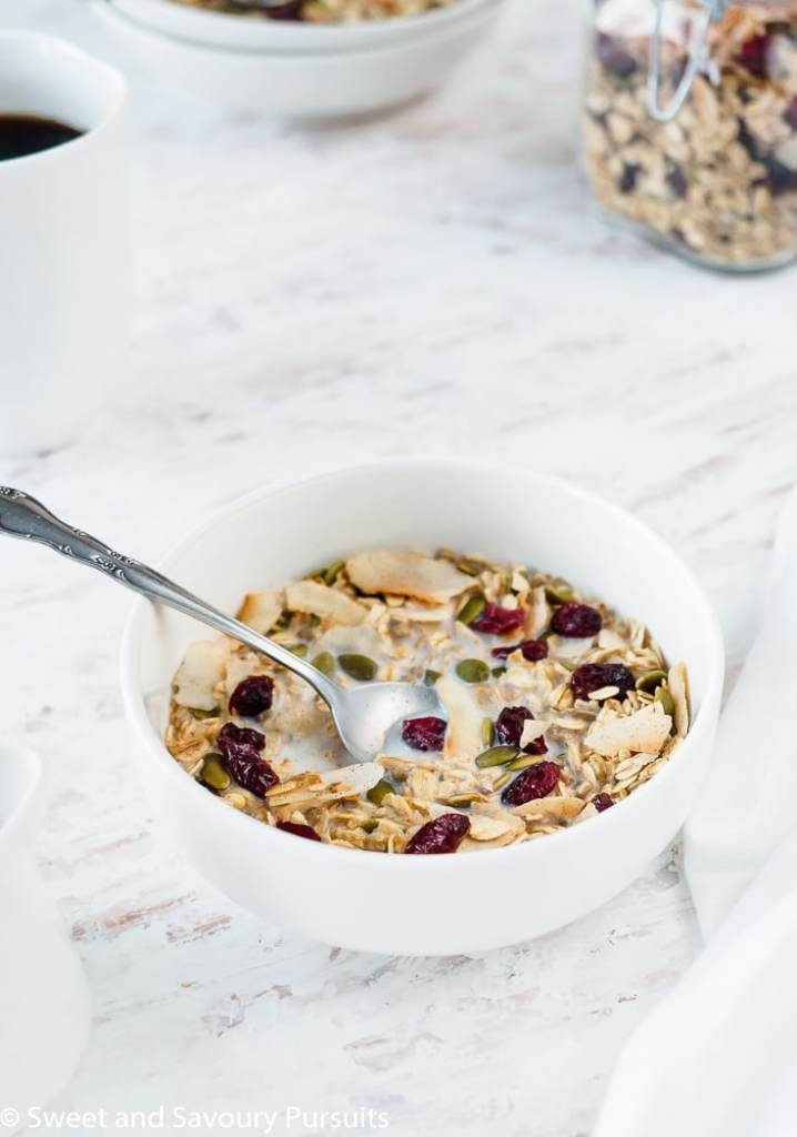 Bowl of homemade muesli made with oats, flaked coconut, pumpkin seeds, sunflower seeds and dried cranberries with milk.
