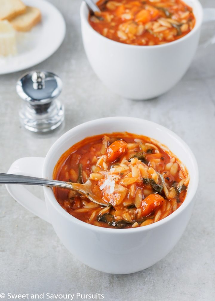 Tomato Orzo Soup with freshly grated Parmesan cheese in large white mug.