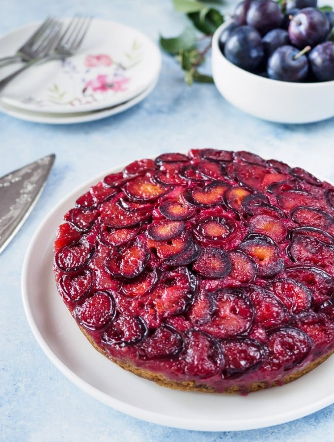 Plum Upside Down Cake on white dish with fresh plums in background.