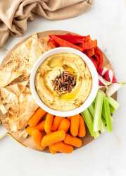 Platter of Caramelized Onion Hummus served with vegetable and pita chips.