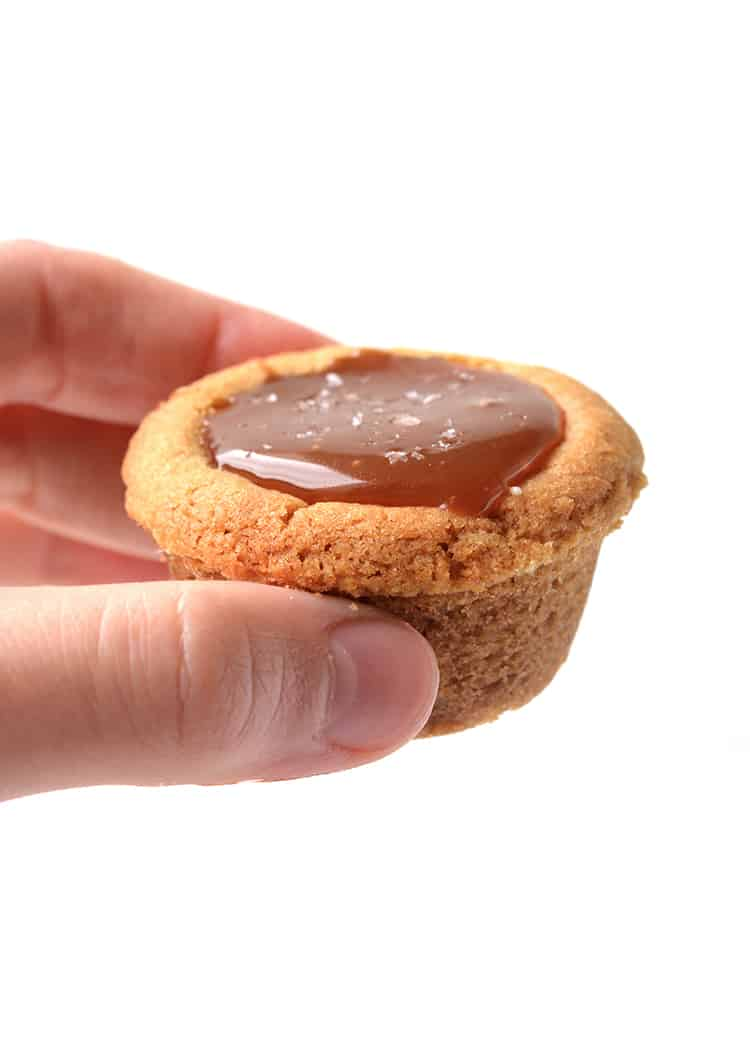 Hand holding a cookie cup filled with caramel sauce
