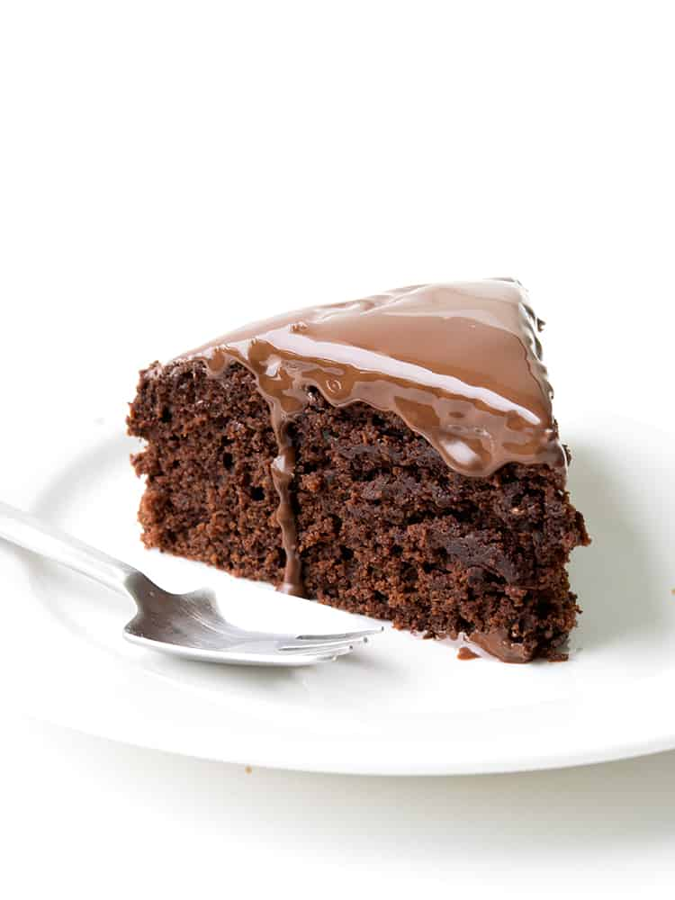 A slice of Dairy Free Chocolate Cake on a white plate