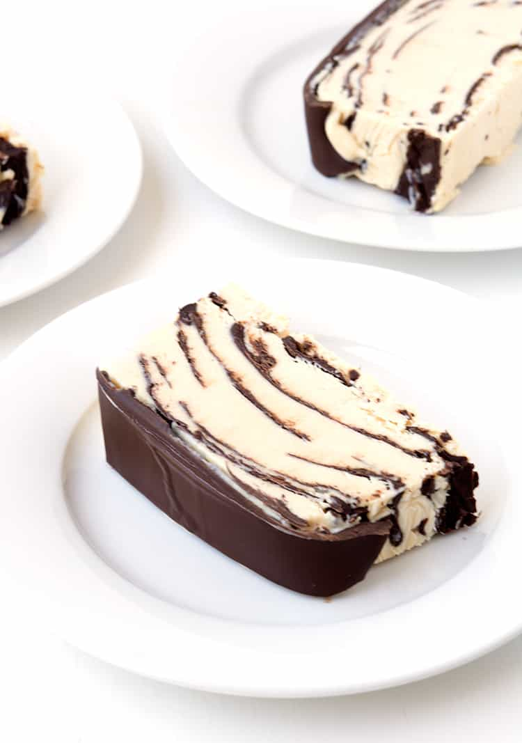 Slices of peanut butter ice cream cake on white plates