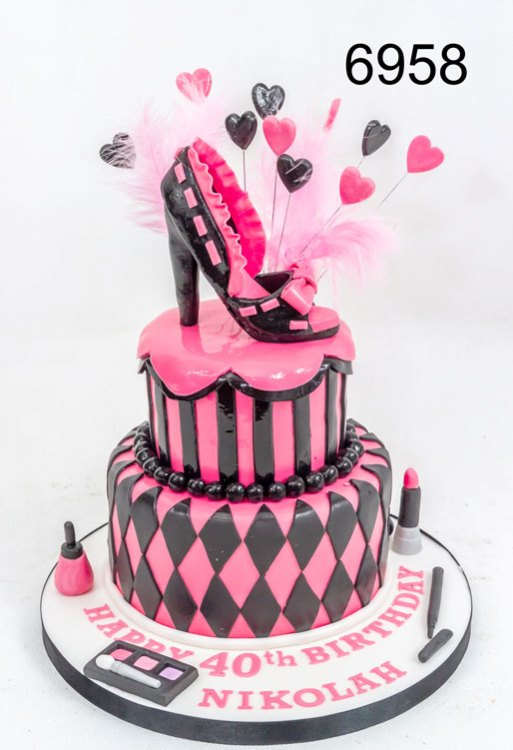 2 tier pink & black cake with make-up and a 3D shoe on top