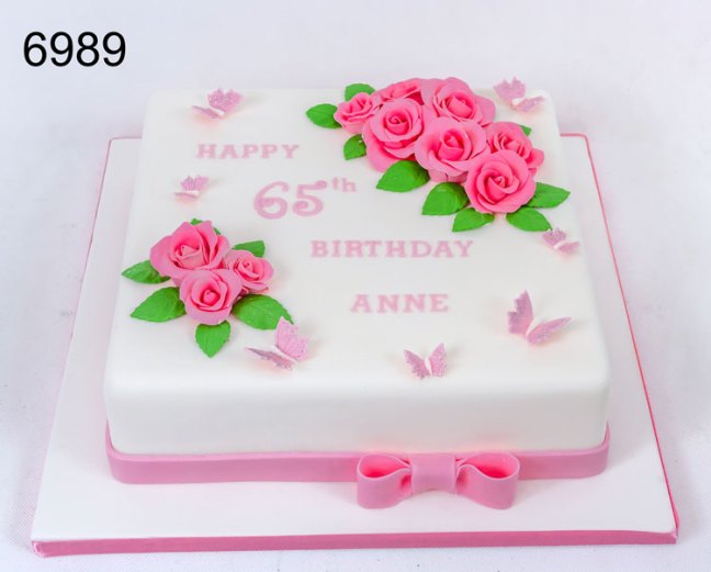 White & pink 65th birthday cake with pink rose sprays