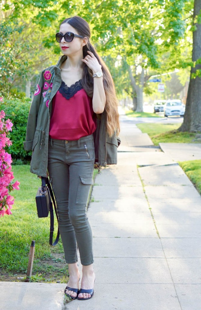 A colorful outfit is challenging to pull off, but the green khaki pants, red silk top and embroidered anorak work together because the colors compliment each other and each of the items is classy and fit well.