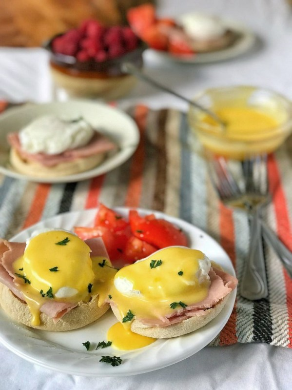 Eggs Benedict on white plate with Hollandaise and table set