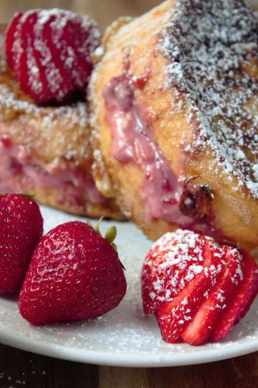 Thick slices of cinnamon-vanilla french toast are filled with strawberries and sweet cream cheese and blanketed in powdered sugar in under 20 mins. www.sweetteaandthyme.com