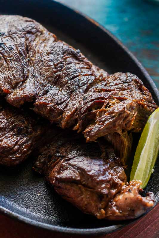Close up of seared carne asada with a wedge of lime