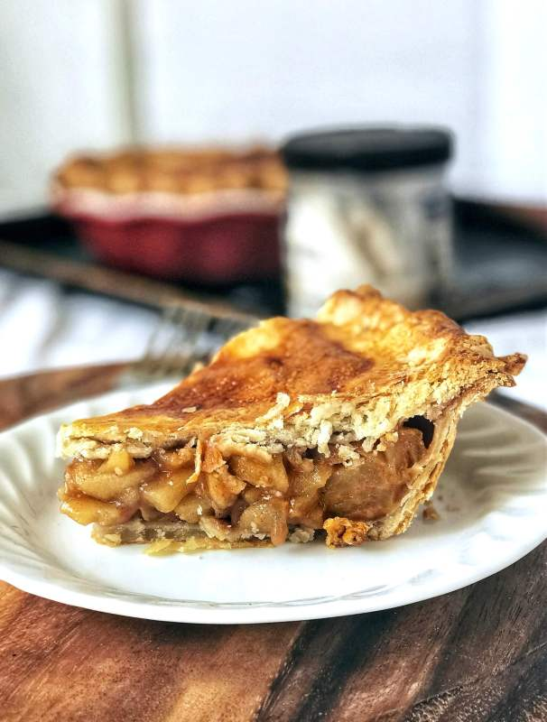 Side view of slice of apple pie. Apple pie from scratch that slices beautifully with amazingly flaky crusts, spiced apple filling that holds its shape, and is perfect for any holiday!