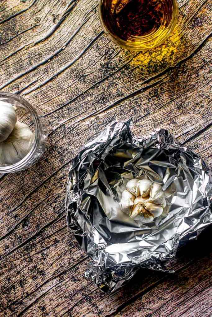 overhead shot of garlic ready to roast in foil and olive oil on wooden table