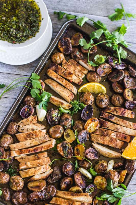 """Dinner is as easy as """"marinate and throw on a sheet pan"""". Sheet pan mojo chicken and the potatoes are full of garlicky, citrusy flavor thanks to the mojo and served with herbaceous chimichurri. Dinner is as easy as """"marinate and throw on a sheet pan""""."""