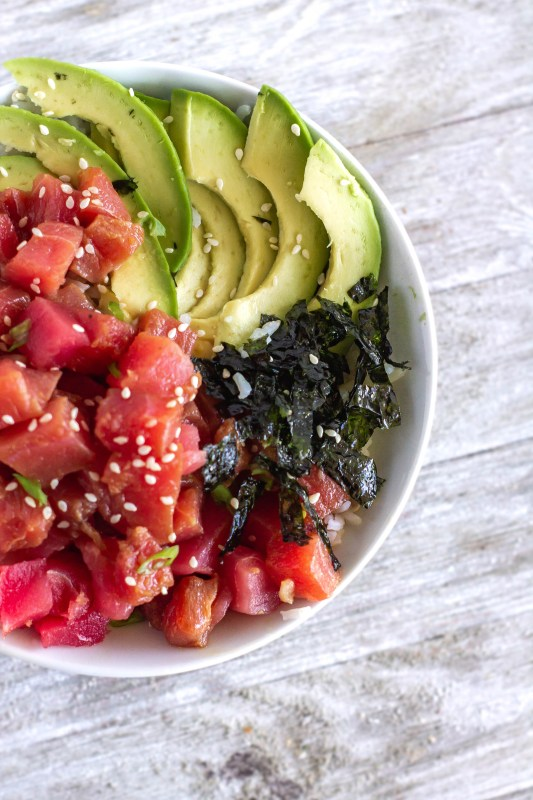 Overhead shot of bowl of marinated and fresh ahi tuna poke with strips of nori seaweed, slices of avocado and garnished with sesame seeds on Sweet Tea and Thyme | www.sweetteaandthyme.com