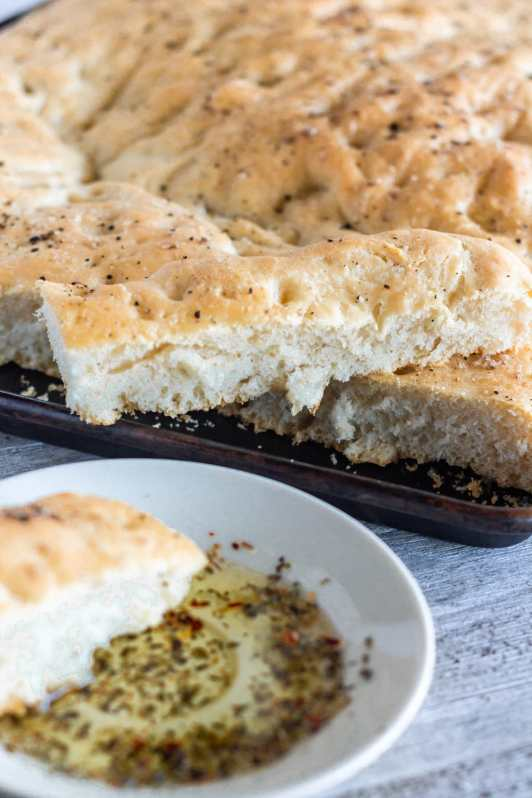 This delicious focaccia bread is so easy to make, has a crispy bottom and fluffy insides, and is beautifully flavored with good extra virgin olive oil, flaky sea salt, and cracked black pepper.