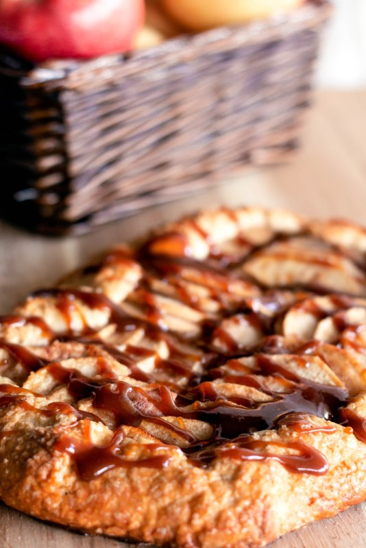 Close up of the crust of caramel apple galette on a wooden board on Sweet Tea and Thyme | www.sweetteaandthyme.com