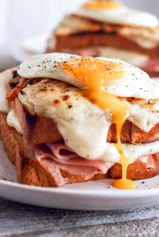 Croque Madame sandwich on a plate with the cheese sauce toasted on the sandwich and a fried egg on top, the egg yolk is running down the side of the sandwich