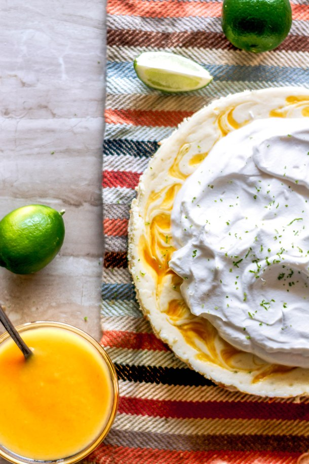 An easy, creamy, decadent mango margarita cheesecake recipe with swirls of mango coulis and all your favorite margarita flavors.