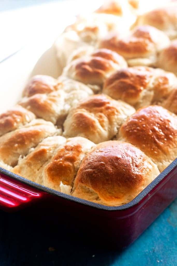 backlit shot of golden brown baked dinner rolls in pan