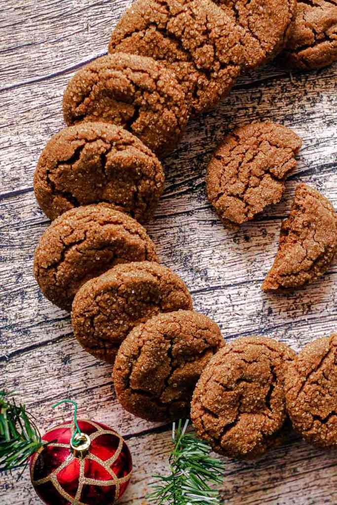 gingersnap cookies laying on a wooden board in a circle, with a cookie broken in half in the middle