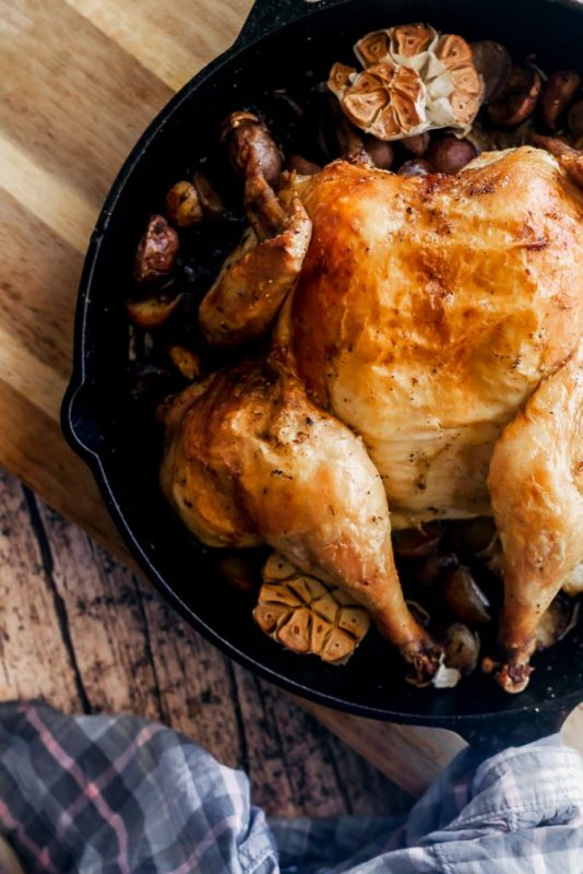 overhead view of spatchcock roast chicken in cast iron pan on wooden cutting board