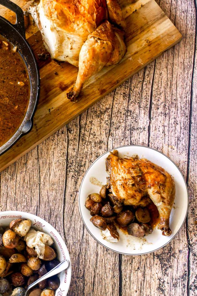 plate of roast chicken leg with potatoes and sauce