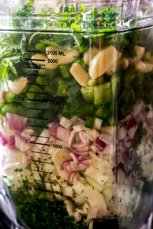 a blender full of sofrito ingredients, the onions, herbs, garlic and peppers are all layered