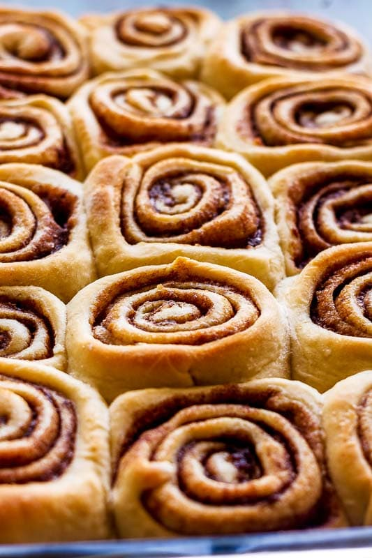 a close view of baked cinnabon cinnamon buns in a baking dish
