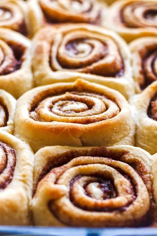 close up of a perfect cinnamon roll among a pan of better than cinnabon cinnamon rolls