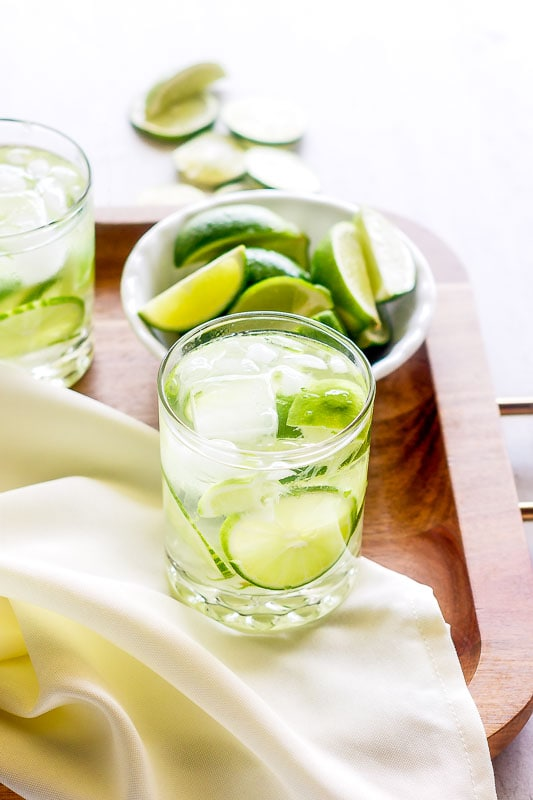 two glasses of caipirinha sit on a wood platter with a cream napkin and bowl full of limes