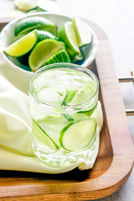 a glass of caipirinha sits on a wood tray with a bowl of limes