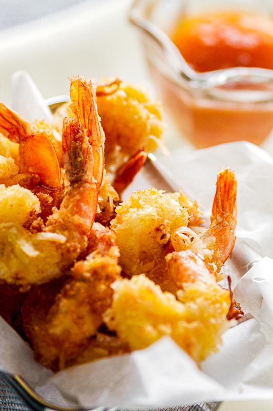 close up of fried jumbo coconut shrimp in a metal frying basket