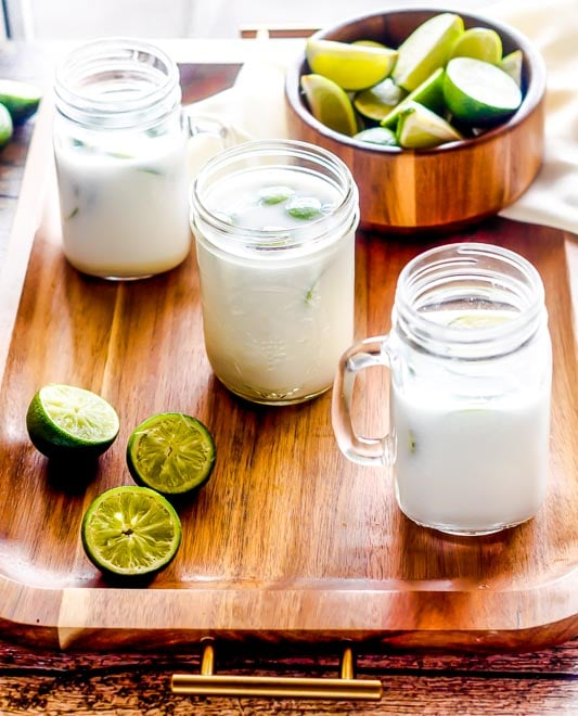 a tray holds three mason jars of hard brazilian limeade, squeezed limes, and a bowl of limes