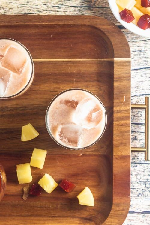 overhead view of starbucks iced guava passionfruit drink on a platter with pineapple