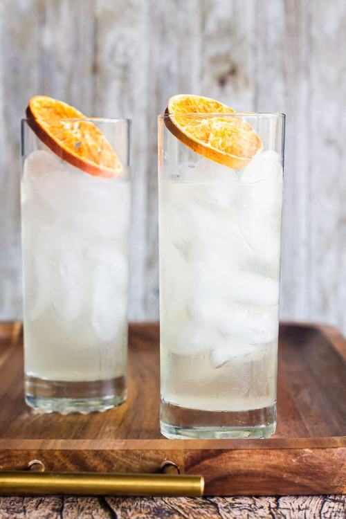 side view of two yuzu tom collins drinks on a wood platter garnished with dried orange slices