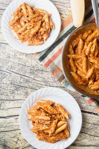 two plates and a pan of penne alla vodka are on a wooden table