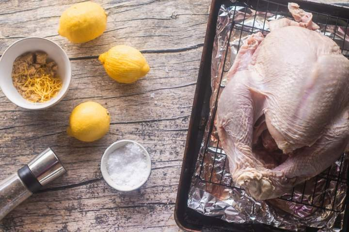 a fresh turkey sitting on a wire rack and salt, pepper, lemon, and brown sugar on a wooden table for dry brining