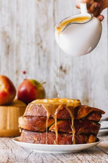 apple cider caramel syrup being poured onto apple butter babka french toast