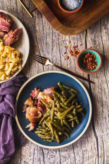 an overhead shot of green beans, ham hock, mac and cheese, and red pepper flakes.