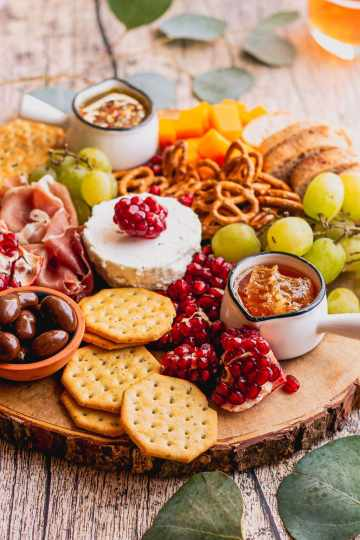 a raw edge wood platter has honey with honeycomb, almonds, crackers, goat cheese, and fresh fruit